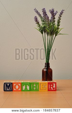 Mother spelled with colorful alphabet blocks and lavender in the background