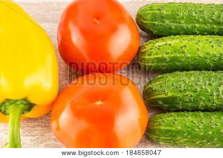 Tomatoes, Yellow Bell Pepper And Cucumber On Light Natural Wooden Background.