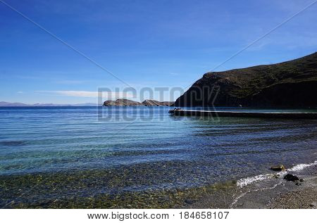 A private beach with mountain background, blue skies and blue waters of Lake Titicaca on Isla Del Sol