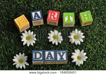 Earth day spelled with colorful alphabet blocks isolated on artificial grass and white daisies