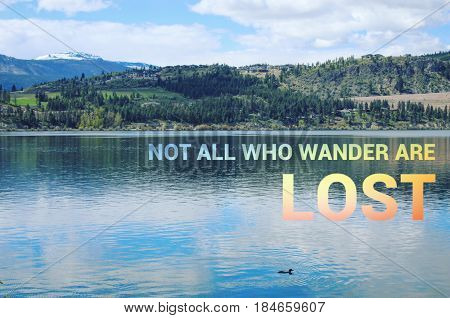 Scenic lake landscape with duck swimming in calm water and colorful text. Not all who wander are lost.