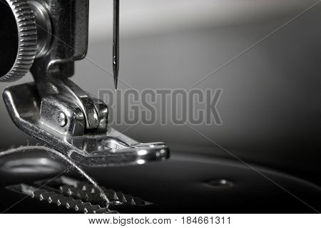 Get Needled: Macro photograph of part of a 1940's sewing machine. Sharp, detailed photo of the needle and pusher. Background layer suitable for multiple business and industrial applications or as wall hanging.