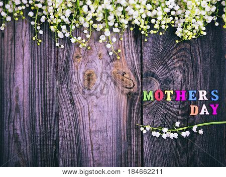 bouquet of fresh lilies of the valley on a gray wooden surface next to the mother's day inscription an empty space on the left