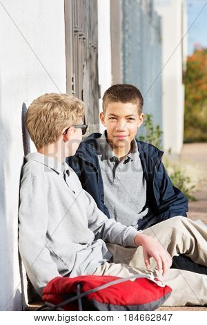 Two Male Youth Friends Sitting Outside