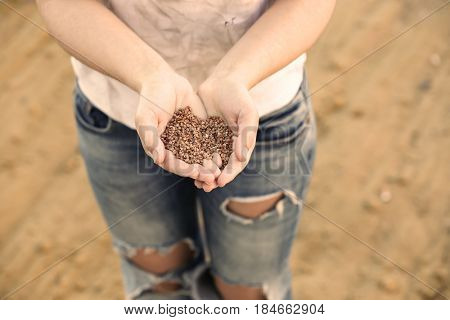 Poor woman holding palm of buckwheat