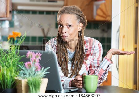 Unimpressed Woman In Kitchen With Compute