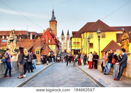 Wurzburg, Germany - April 21, 2013: Walking people on the Old Main Bridge over the Main river in the Old Town of Wurzburg in the evening
