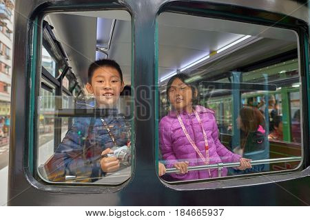 HONG KONG - CIRCA DECEMBER, 2015: children in a tram. Hong Kong Tramways is one of the earliest forms of public transport in the metropolis.