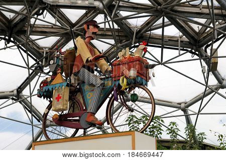 Bodelva, Cornwall, Uk - April 4 2017: Statue Of A Delivery Man On A Bicycle At The Eden Project In C