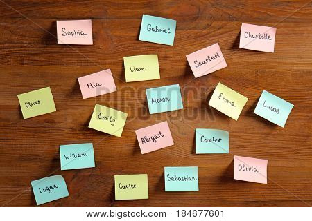 Paper stickers with different names on wooden background