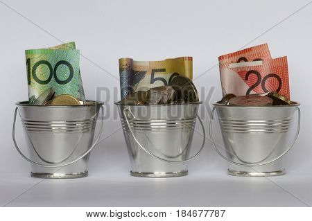 A row of buckets containing Australian dollars and coins.