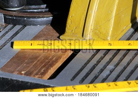 Yellow folding ruler, in inches on a saw bench