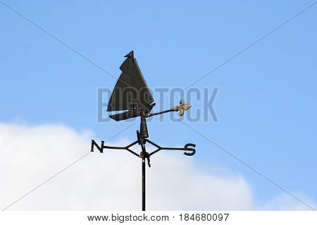 Sailboat weather vane with blue sky and white cloud