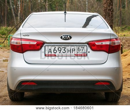 Smolensk, Russia - April 29, 2017: New Kia Rio parked in the forest, back side.