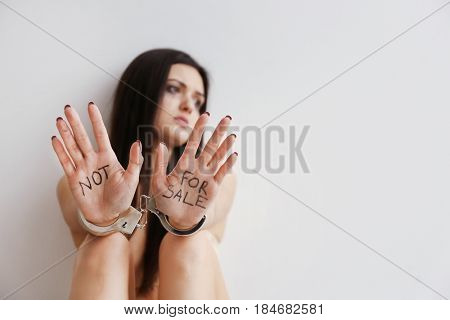 Woman in handcuffs on light background