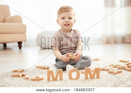 Cute little child and word MOM composed of wooden letters on floor at home