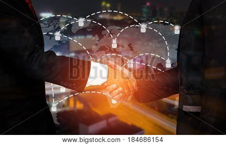 double exposure of businessman handshake with world map social media network connection successful business meeting on blurred night city background sunlight color tone effect.