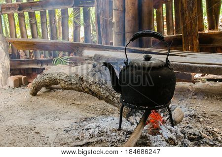 old vintage kettle with bunch of burning firewood to boil water in the old aluminum kettle with the scene of the shade of the housing of the hill tribes soft focus selective focus culture concept