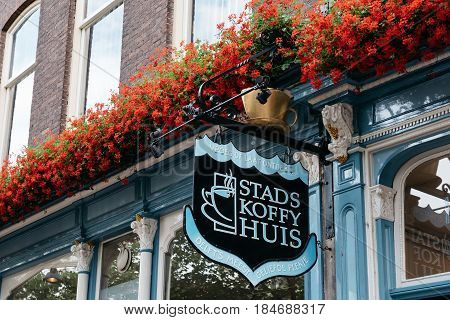 Delft Netherlands - August 3 2016: Old retro signboard of a coffee shop in Delft decorated wih red flowers