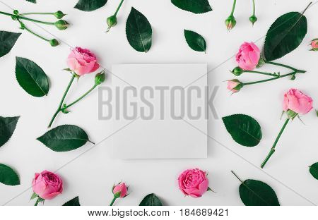 Blank card with pink roses and green leaves on a white background. Flat lay top view