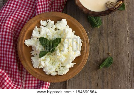 dairy product cottage cheese in brown ceramic bowl. Curd in brown bowl on blue napkin. Fresh cottage cheese in bowl with spoon on vintage wooden tabledoor