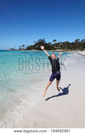 A boy jumping at the beach at Binalong Bay - Tasmania. This east coast area of Tasmania is home to some of the most beautful beaches in the world.