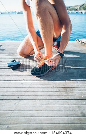 Vertical outdoors shot of man tighten the sneakers before training.