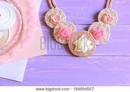 Beautiful women's necklace. Women's necklace made of ribbons, cords and felt. Materials to create jewelry on a wooden table. Floral summer accessory. Top view