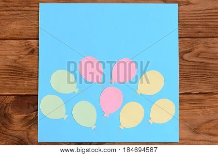 Making a card with paper air balloons. Step. Lesson for children. Card with paper air balloons isolated on a wooden table. Preschool and kindergarten crafts activities. Closeup. Top view