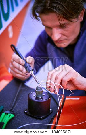 The electrician performs the soldering of wires with a soldering iron. poster