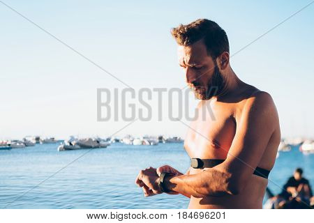 Shirtless man standing at ocean and setting HRM device on his hand. Horizontal outdoors shot.