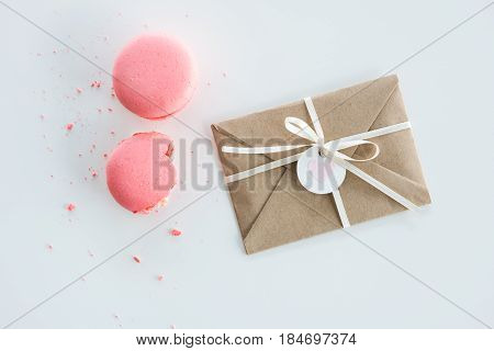 Top View Of Decorative Kraft Envelope With Bow And Pink Macarons Isolated On White, Wedding Invitati