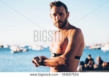 Fit shirtless man setting the heart-rate monitor and looking at camera.