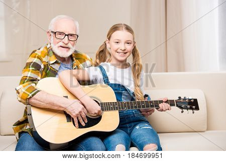 Happy Grandfather And Granddaughter Sitting On Sofa With Guitar And Smiling At Camera