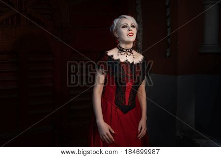 Woman with a vampire fangs she is dressed in a red dress with lace.