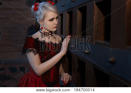 Sad woman in a vintage dress with lace on her neck is an ornament.