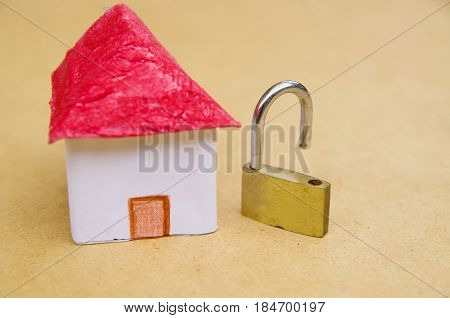 A small and beautifl house model concept of good segurity with an unlock padlock, medium property protection.
