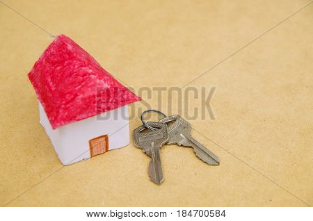 A small and beautiful house model made of paper with a couple of keys .