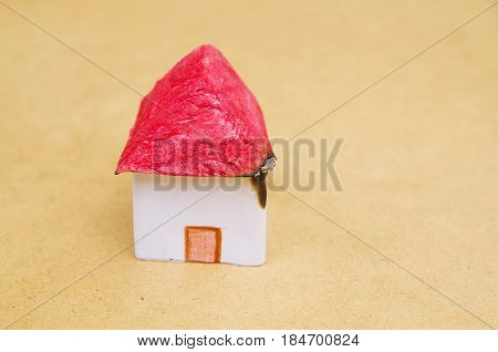 A beautiful and small house model made of paper with a wooden background, burning housing a weak property protection.