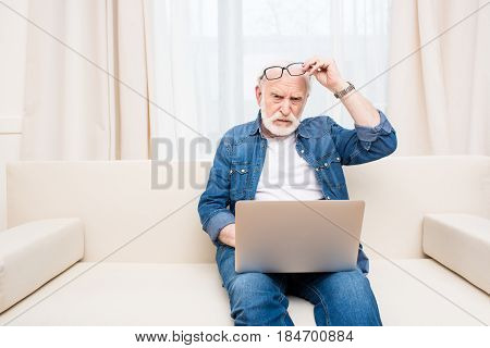 Frowning Senior Man With Eyeglasses On Forehead Using Laptop On Sofa