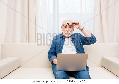 Shocked Senior Man Sitting With Laptop On Knees And Holding Eyeglasses