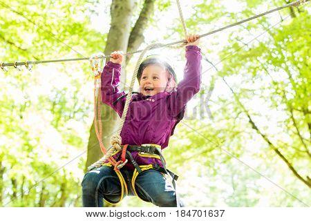 Girl climbing in high rope course enjoying the adventure
