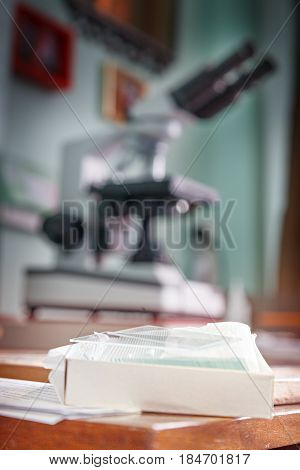 Cover glass for microscope. Glass lying on the edge of the table. In the background is seen the microscope. Laboratory microscope is defocused. A set of laboratory cover glass in a cardboard box.
