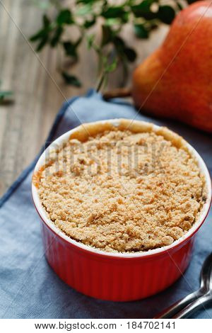 Close-up of a portion dessert pear crumble pie in a red bowl on a wooden table.