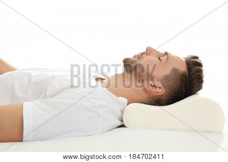 Young man sleeping on bed with orthopedic pillow against white background. Healthy posture concept