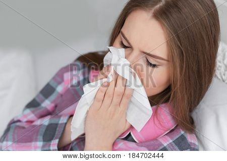 Ill woman with tissue in bed at home