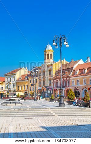 Brasov, Romania - March 24, 2015: The Orthodox Church of the Birth of the Mother of God at Council Square -Piata Sfatului - in downtown of Brasov and people near it
