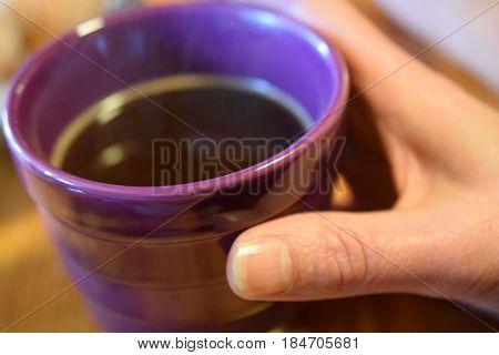 Woman hand holding a purple coffee mug.