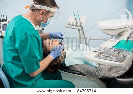 Male Dentist With Dental Tools - Mirror And Probe Treating Patient Teeth At Dental Clinic Office. Me