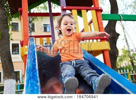 Cheerful laughing little boy pulling off a children's roller coaster in the park at noon